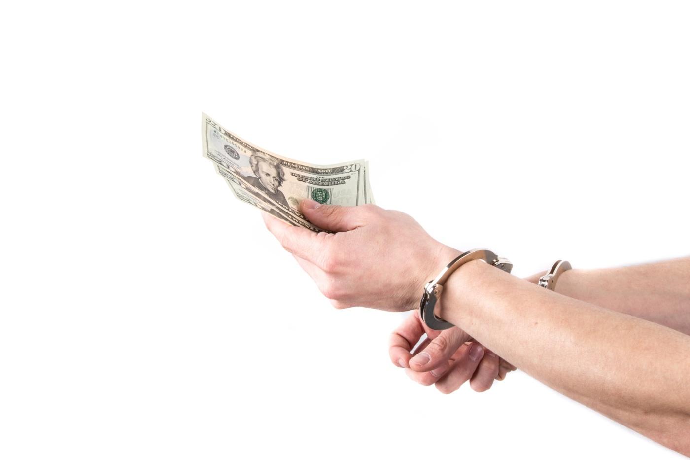 hands-in-handcuffs-hold-money-14626079489uy